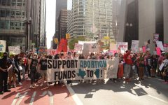 Marchers carrying a sign paused during the Rally to Defend Abortion Access in Chicago, Ill. on Oct. 2, 2021