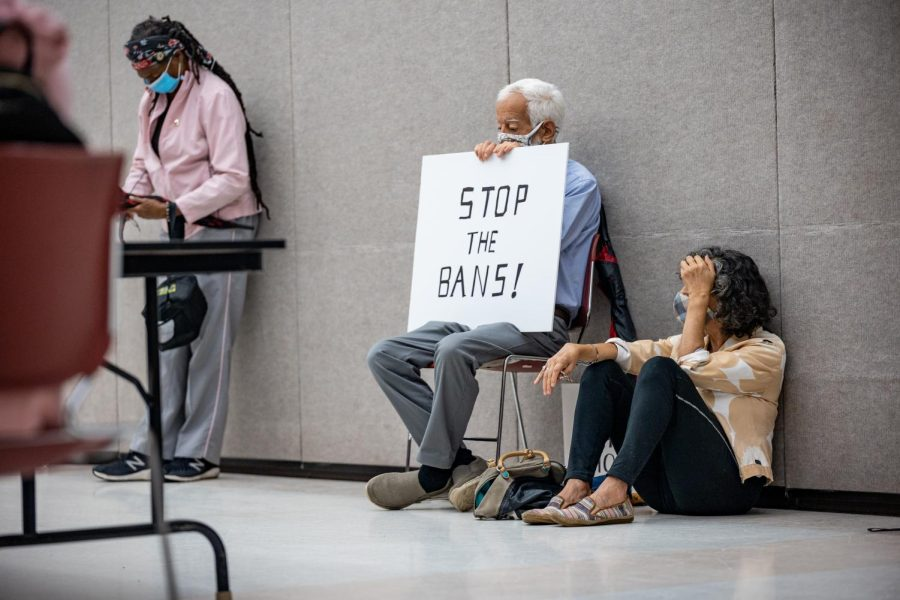 Activists listen to speakers at the March for Reproductive Rights while holding a sign that reads STOP THE BANS! Oct. 2, 2021 at the Carbondale Civic Center in Carbondale, Ill.