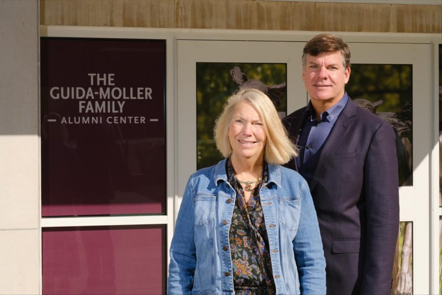 Julie Guida and her brother, Scott Moller, pose beside the new Alumni Center named for them after a $500,000 gift.